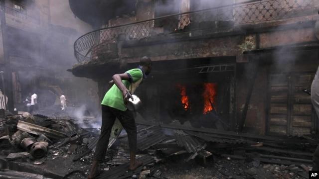 Un homme essayant de contenir l'incendie d'une maison et un entrepot a Lagos Island, Lagos, Nigeria, December 26, 2012.