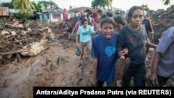 Seorang perempuan menangisi kerabatnya yang ditemukan tewas akibat banjir bandang yang dipicu hujan lebat di Flores Timur, Nusa Tenggara Timur, 6 April 2021. (Foto: Antara/Aditya Pradana Putra via REUTERS)