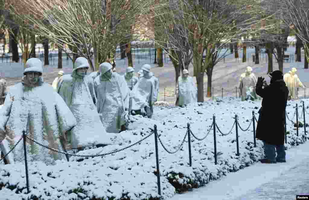 A man photographs the Korean War Veterans Memorial after a heavy snow storm in Washington D.C., Jan. 3, 2014.