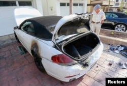 A man looks at a BMW car that was damaged by a lightning strike on Haynes Lane in a residential area of Redondo Beach, California, July 27, 2014.