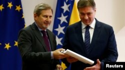 European Union enlargement commissioner Johannes Hahn hands the Questionnaire of the European Commission to Bosnian Prime Minister Denis Zvizdic in Sarajevo, Bosnia and Herzegovina, Dec. 9, 2016.