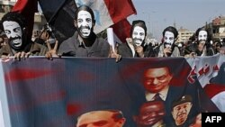 Protesters wear masks depicting slain Coptic activist Mina Daniel while carrying a banner picturing Egypt's military rulers and ousted President Hosni Mubarak as they march in the suburb of Shobra, on their way to join a rally in Tahrir Square in Cairo, E