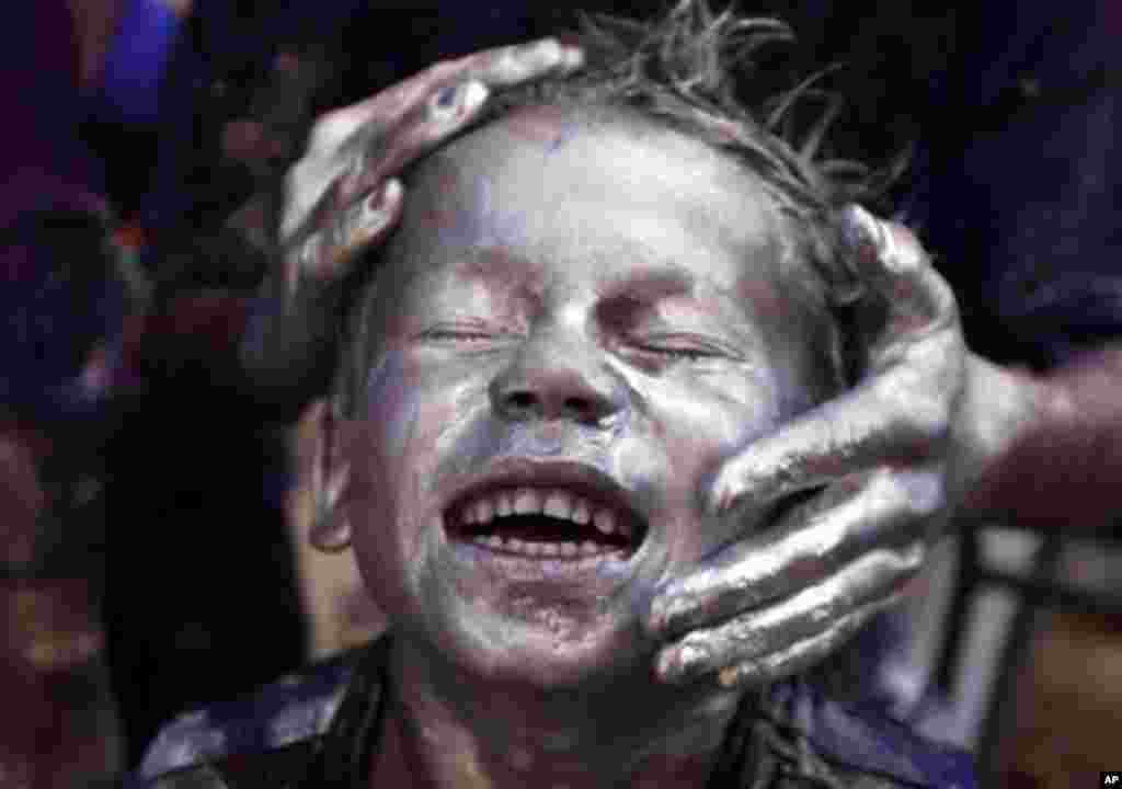 A young Indian boy is smeared with colored powder and glitter on his face during Holi celebrations in Allahabad, India, Friday, March 9, 2012. Holi, the Hindu festival of colors, also heralds the coming of spring. (AP Photo/Rajesh Kumar Singh)
