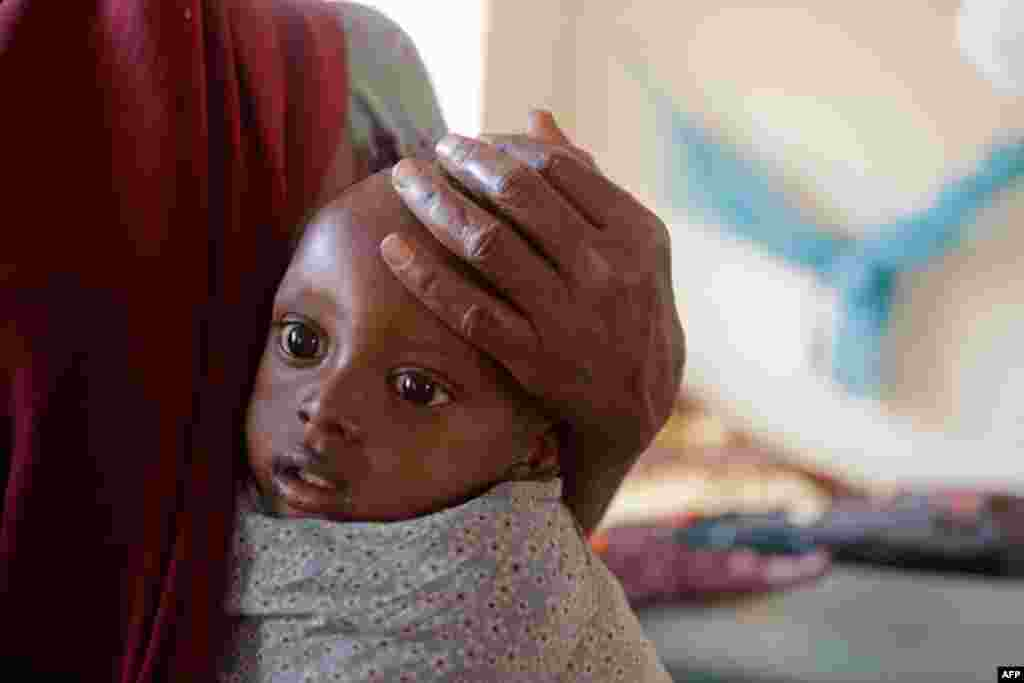 July 23: A woman holds her child at a ocal hospital where children receive treatment for malnutrition at the border town of Dadaab, Kenya. The drought in the Horn of Africa and the famine in Somalia has left more than two million children at risk of star