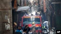 Sebuah mobil pemadam berdiri di dekat lokasi kebakaran di sebuah gang yang dipenuhi kabel listrik dan terlalu sempit untuk diakses oleh kendaraan, di New Delhi, India, Minggu, 8 Desember 2019. (Foto: AP)
