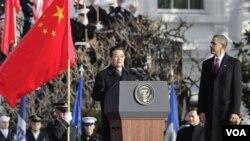 Presiden Barack Obama memperhatikan Presiden Hu Jintao memberikan pidato dalam upacara penghormatan di Gedung Putih, Rabu 19 Januari 2011.