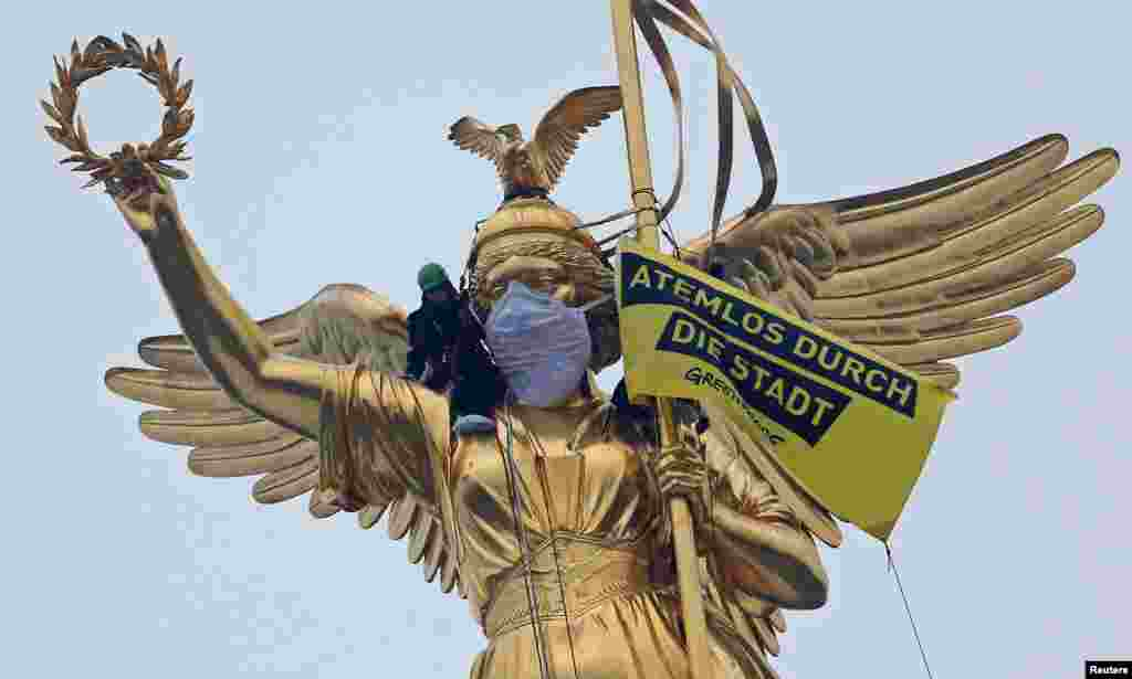 "Greenpeace activists climb the Golden Victoria monument and install a banner ""Breathless through the city"" to protest against air pollution in Berlin, Germany."