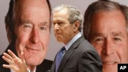 Cựu Tổng thống George W. Bush đi ngang qua một bức chân dung của chính mình và cha của ông, cựu Tổng thống George H.W. Bush.