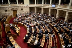 Greek lawmakers attend an emergency parliament session for the government's proposed referendum in Athens, June 27, 2015.
