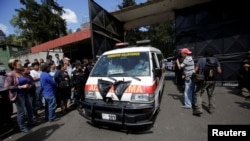 FILE - An ambulance carrying the bodies of those killed in the fire exits the Virgen de Asuncion home, in San Jose Pinula, on the outskirts of Guatemala City, Guatemala, March 8, 2017.