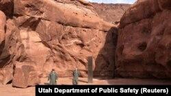 Les membres de l'équipage du bureau aéronautique du département de la sécurité publique de l'Utah et de la division des ressources fauniques de l'Utah marchent près d'un monolithe métallique qu'ils ont découvert dans une région éloignée de Red Rock Countr