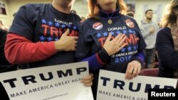FILE - Supporters of U.S. Republican presidential candidate Donald Trump hold their hands to their chest as the national anthem is played at a campaign rally in Concord, New Hampshire, Jan. 18, 2016. As the only Republican left in the field, Trump has now all but clinched the Republican party's nomination.