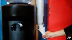 资料图片:2018年9月4日,底特律一所小学的员工用杯子接瓶装水。底特律学区将在其所有学校安装水站,此前一半以上的测试结果显示水中的铜和铅含量很高。