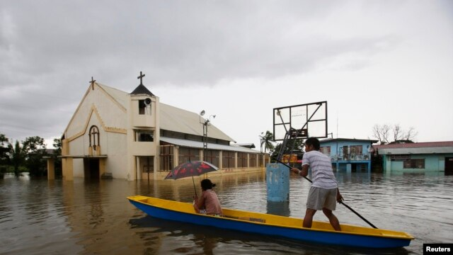 A man ferries a passenger on a boat past a church along a flooded road brought by moonsoon rains and reinforced by tropical storm Trami, in Calumpit, Bulacan, north of Manila, August 21, 2013.