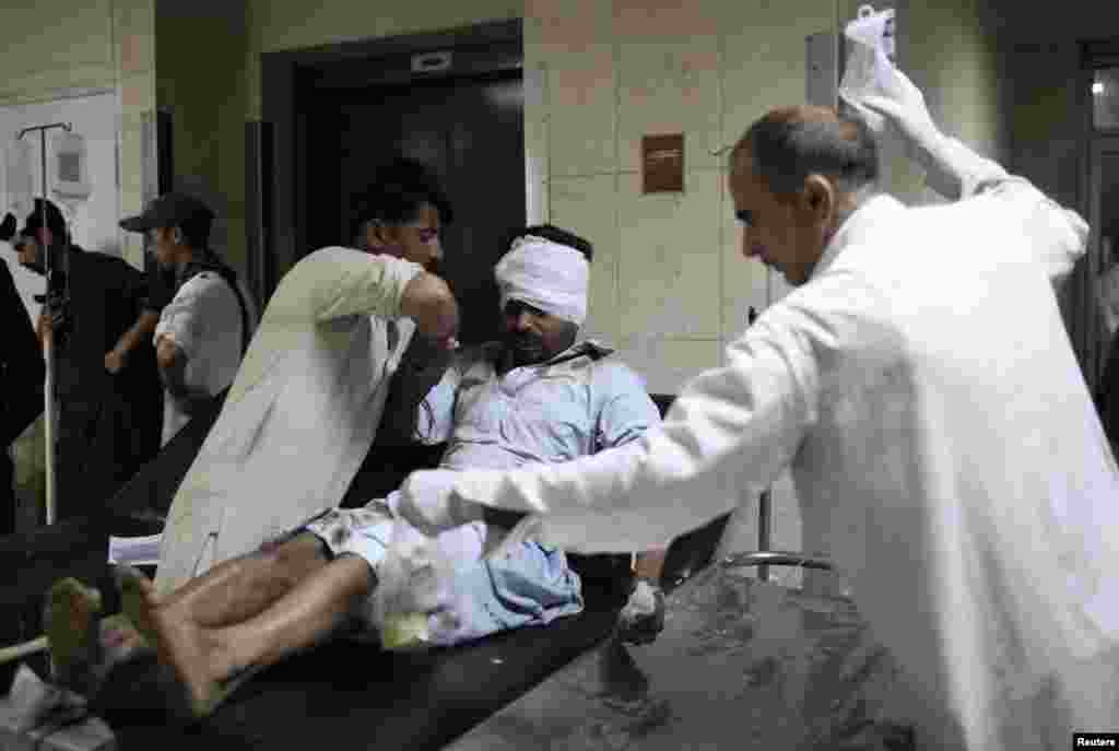Medics attend to a man wounded in a bomb blast at a vegetable market in Islamabad April 9, 2014.