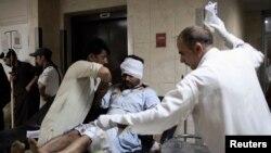 Nhân viên y tế đưa nạn nhân đến bệnh viện, sau vụ nổ trong ngôi chợ rau quả ở thủ đô Islamabad, Pakistan, 9/4/14