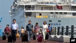 Para penumpang kapal pesiar mewah China, Henna, meninggalkan kapal tersebut menuju bandara Jeju di Korea Selatan (15/9). Sekitar 2.300 penumpang dan awak kapal sempat tertahan selama dua hari di Korea Selatan, ketika mahkamah distrik Jeju memerintahkan agar kapal itu ditahan di pelabuhan Jeju, Korea Selatan, Jumat sore.