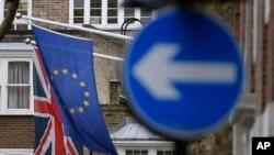 FILE - An EU flag hangs beside the Union flag at Europa House in London, Feb. 17, 2016.