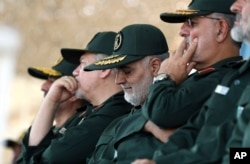 In this June 30, 2018 photo, released by an official website of the office of the Iranian supreme leader, Gen. Qassem Soleimani, center, who heads the elite Quds Force of Iran's Revolutionary Guard attends a graduation ceremony.
