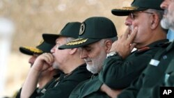 In this June 30, 2018 photo, released by an official website of the office of the Iranian supreme leader, Gen. Qassem Soleimani, center, who heads the elite Quds Force of Iran's Revolutionary Guard attends a graduation ceremony of a group of the guard's o