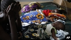 Unidetified mother watches over malari-stricken child, Siaya hospital in Western Kenya, Nov. 9, 2012.