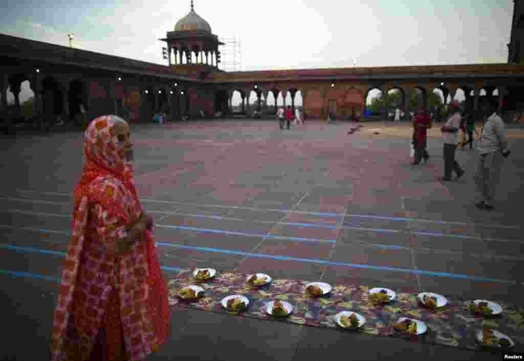Seorang perempuan menunggu makanan berbuka puasa di Jama Masjid, New Delhi.