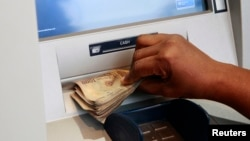 Woman takes Nigerian Naira from automated teller machine in Ikeja district of the country's commercial capital, Lagos, Nov. 12, 2014.