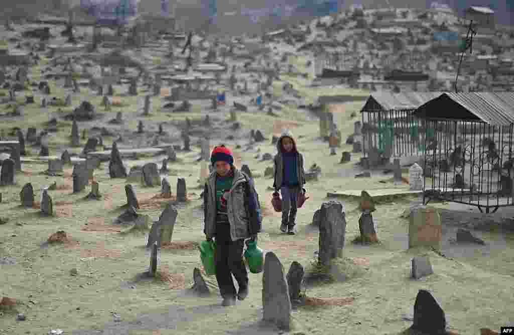 Afghan children who work as water vendors search for customers at the Kart-e-Sakhi cemetery in Kabul.
