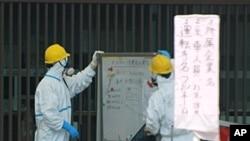 警衛在福島核電廠門前查看報告顯示版