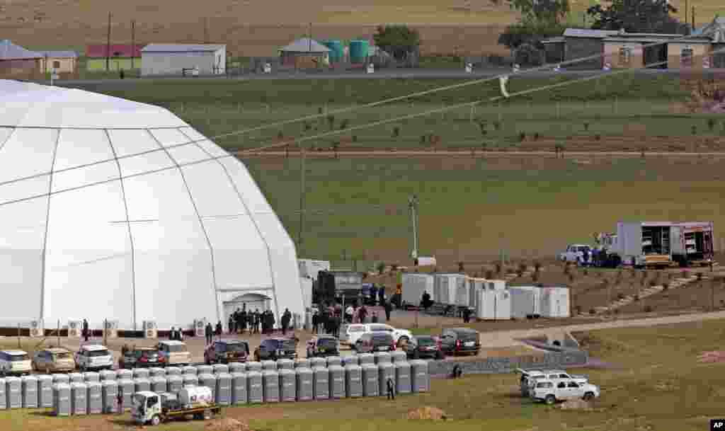 People stand outside the dome where the funeral of former South African president Nelson Mandela is taking place in Qunu.