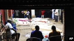 People sit near bodies of relatives killed after gunmen burst into a bar in Gatumba, Bujumbura Rural Province, Burundi, Sept. 19, 2011 (file photo).
