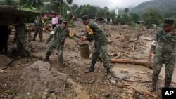 Soldados mexicanos ayudan a remover el lodo y los escombros en deslave en el municipio de Xaltepec, en las montañas de Puebla, México.