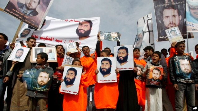 Yemeni protesters hold pictures of people in U.S. detention at a demonstration outside the U.S. Embassy in Sanaa, Yemen, demanding the release of Yemeni detainees in the Guantanamo Bay detention facility, Saturday, Jan. 11, 2014. AP Photo/Hani Mohammed