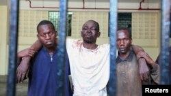 Omar Mwamnuadzi, au centre, chef du Conseil républicain de Mombasa (MRC), mouvement séparatiste, est ramené par deux personnes non-défiées à sa cellule de la cour de la loi avec les membres du groupe à la région côtière du Kenya le 15 octobre 2012.