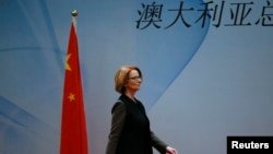 "FILE - Australia's Prime Minister Julia Gillard walks past a Chinese national flag as she arrives at a welcoming lunch during the Australia China Economic and Trade Forum at a hotel in Beijing, April 9, 2013. The Chinese characters read, ""Australia."""