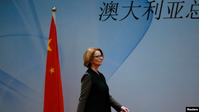"Australia's Prime Minister Julia Gillard walks past a Chinese national flag as she arrives at a welcoming lunch during the Australia China Economic and Trade Forum at a hotel in Beijing, April 9, 2013. The Chinese characters read, ""Australia."""