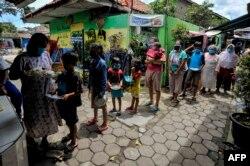 Warga yang mengalami kesulitan keuangan dan dalam karantina karena wabah COVID-19 antre mendapatkan makanan gratis sumbangan masyarakat di Kampung Lio Genteng, Bandung, Jawa Barat, 8 April 2020. (Foto: AFP)