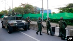 Thai soldiers take up position on a street outside the Center for the Administration of Peace and Order (CAPO) after soldiers were sent in to seize the center Tuesday, May 20, 2014.
