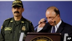 Colombian Defense Minister Luis Carlos Villegas, right, and national Police Chief Gen. Rodolfo Palomino appear before reporters in Bogota to discuss a police helicopter crash that killed 16 officers taking part in a manhunt, Aug. 4, 2015.