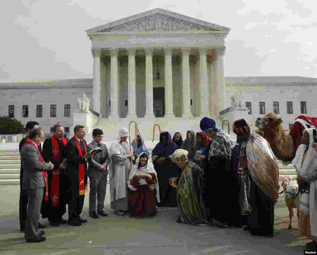 Actores que representan a José y María llevan a un bebé -Jesús- frente a otros actores vestidos como los Reyes Magos durante una escena de la natividad a las afueras de la Corte Suprema y el Capitolio en Washington.