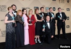 The cast of Downton Abbey, from left, Phyllis Logan, Tom Cullen, Lesley Nicol, Sophie McShera, Joanne Froggatt, Raquel Cassidy, Kevin Doyle,Tom Cullen, Allen Leech, and Jeremy Swift, hold their awards for Outstanding Performance by an Ensemble in a Drama Series during the 22nd Screen Actors Guild Awards in Los Angeles, California on Jan. 30, 2016.