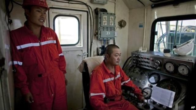 Chinese technicians operate drilling equipment on an oil rig in Paloich, southern Sudan, Nov 17, 2010
