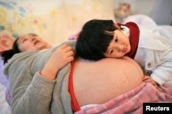 Li Yan(音译)在医院等着生她的第二个孩子,她的大女儿将头放在其肚子上。