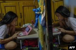 Maria Conception Relloma, mahasiswa yang baru memasuki tahun pertamanya, mulai mengikuti kuliah daringnya dari rumah dengan menggunakan ponsel dan modul pembelajaran tercetak pada pembukaan sekolah di pinggiran kota kota Mandaluyong Manila, 5 Oktober 2020.(Foto oleh Maria Tan / AFP)