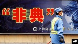 City employee wearing protective mask walks past local government anti-SARS advertisement, Shanghai, 2003.