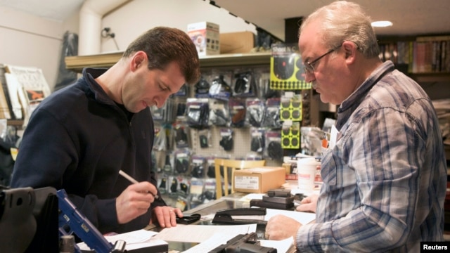 Brian O'Connor (L) of Newtown, Connecticut, fills out paperwork to purchase a Glock 10mm pistol at Chris' Indoor Shooting Range in Guilford, Connecticut April 2, 2013.