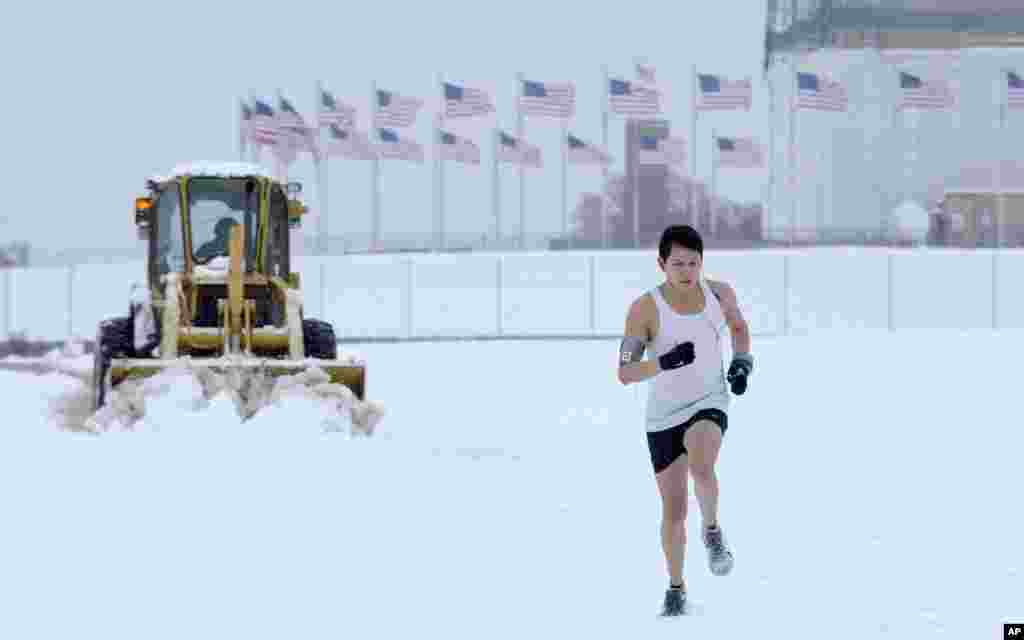 Snow is plowed behind a jogger running on the Washington Monument grounds in Washington. Snow fell in parts of the Mid-Atlantic and Northeast as winter-weary motorists faced another potentially treacherous commute, just days before the start of spring.