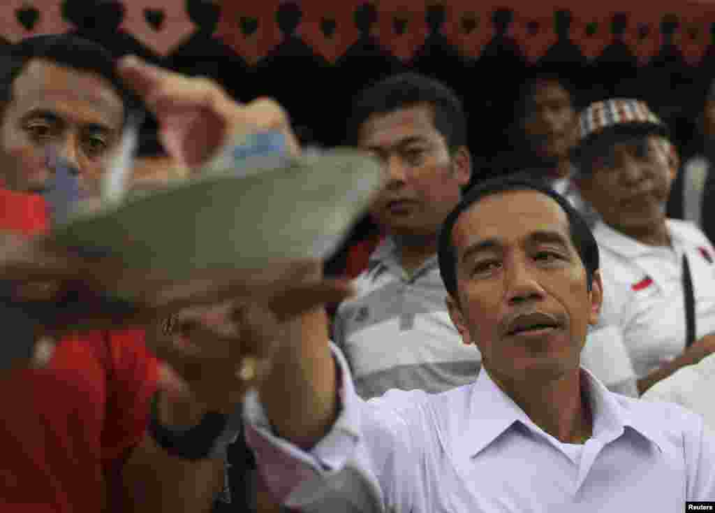 Jakarta governor and presidential candidate Joko Widodo gives donations during lunch with his supporters from the PDI-P party in Jakarta, March 16, 2014.
