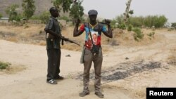 FILE - Members of a civilian vigilante group stand guard at the border with Nigeria in Kerawa, Cameroon, March 16, 2016. Kerawa is on the border with Nigeria and is subject to frequent Boko Haram attacks.