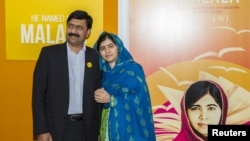 "Activist Malala Yousafzai (R) and her father Ziauddin Yousafzai (L) attends the premiere of ""He Named Me Malala"" at the Ziegfeld Theater in Manhattan, New York, Sept. 24, 2015."